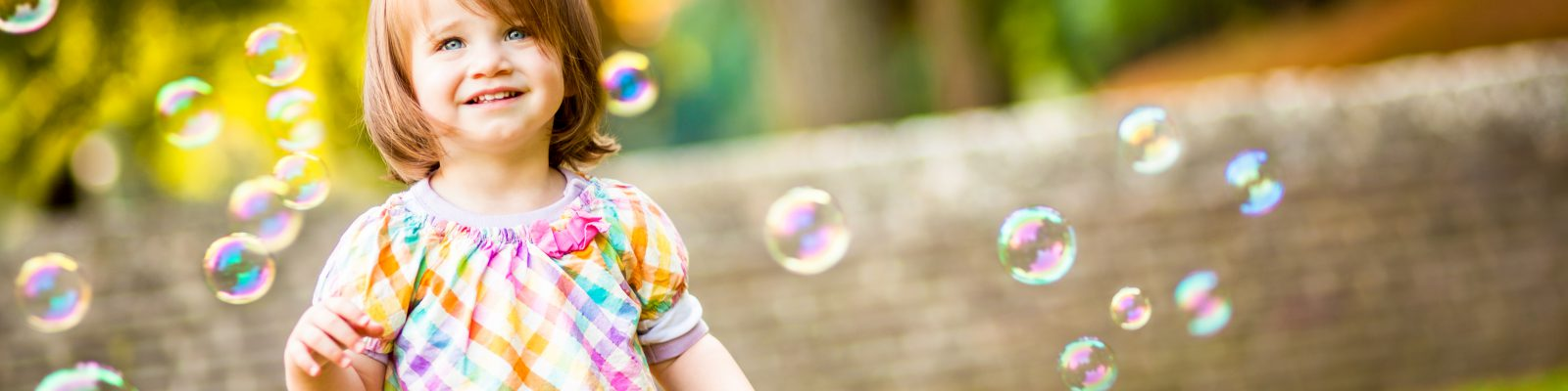 Close-up Of Smiling Little Standing Around Bubbles In Garden